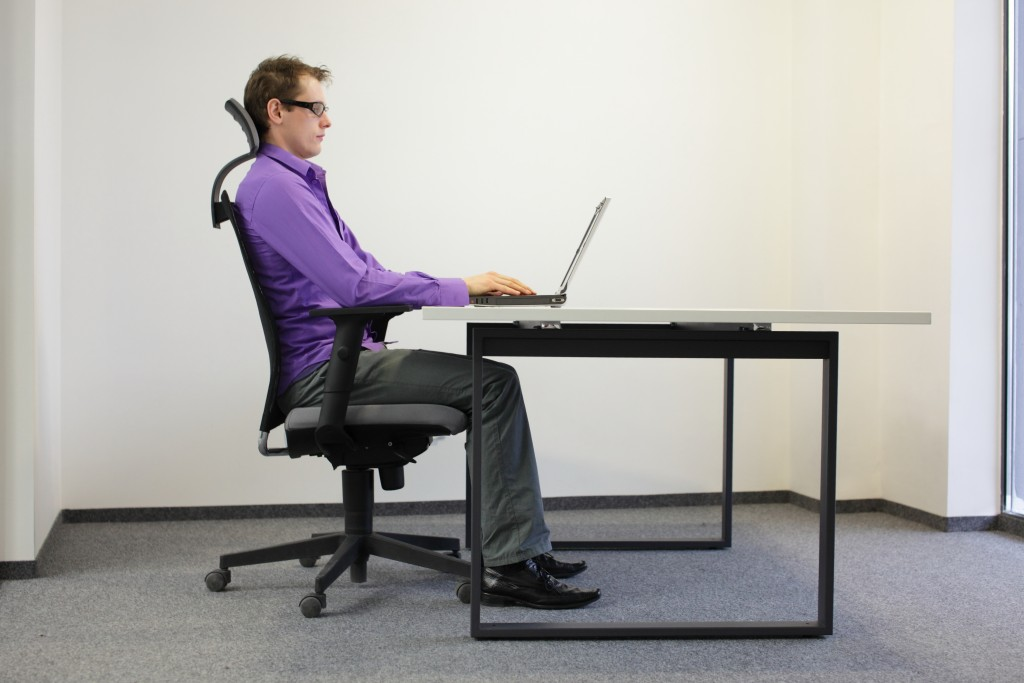 person using a laptop on his desk