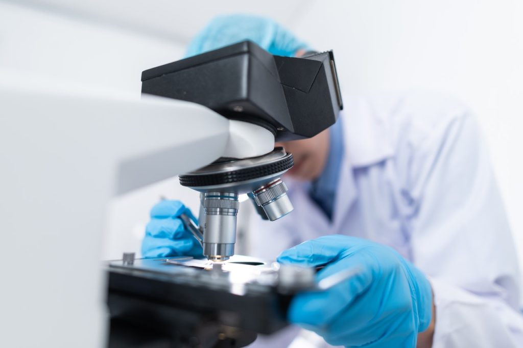 researcher looking at a microscope