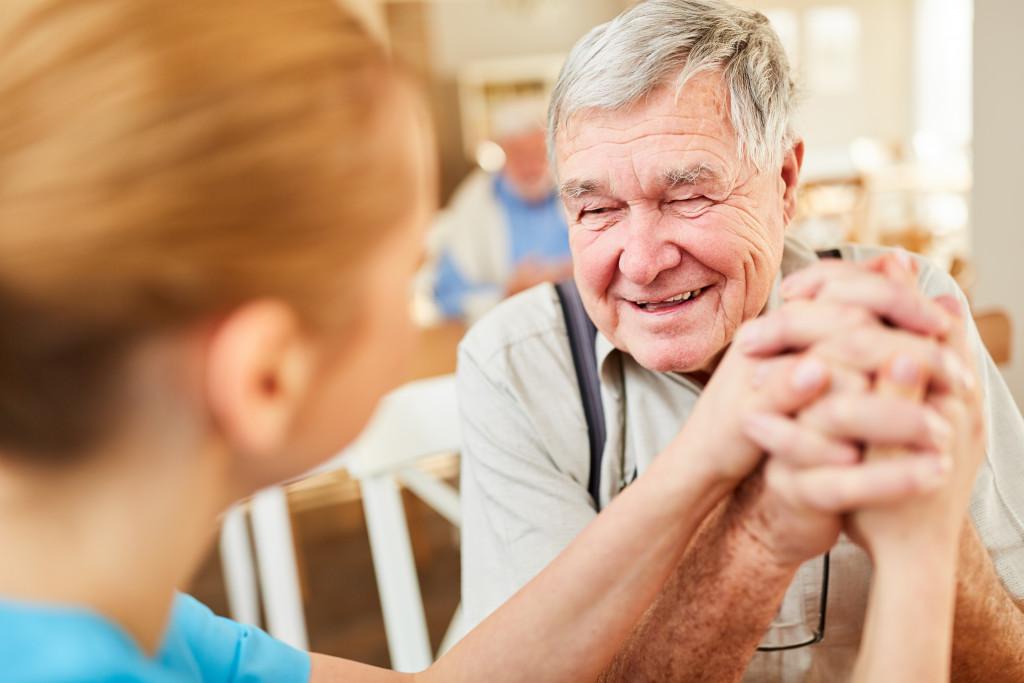 old man holding nurse's hand