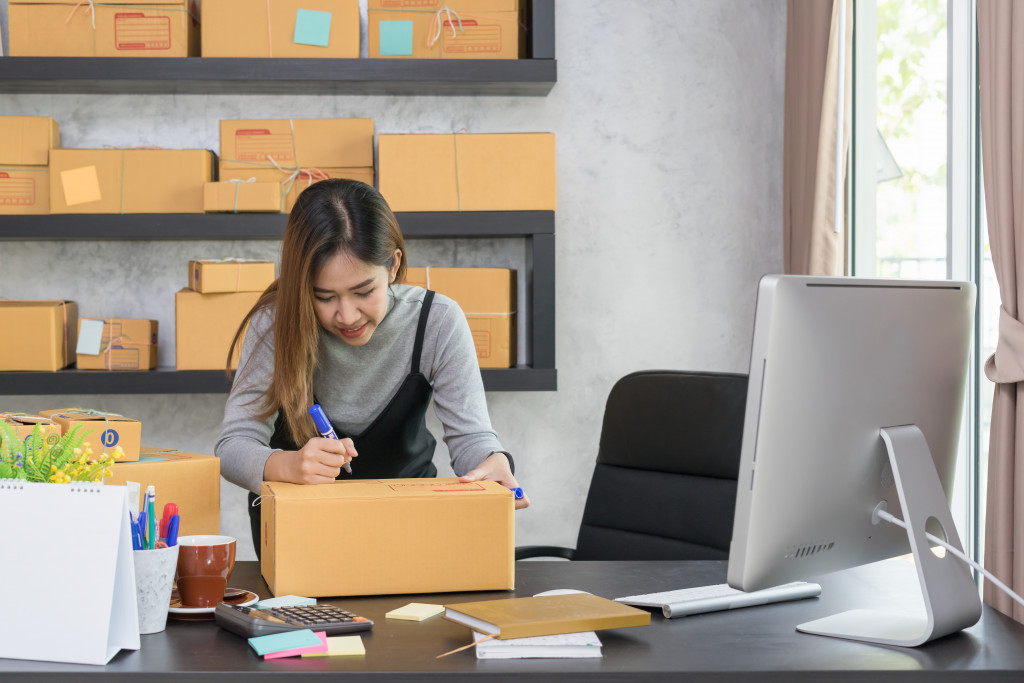 business owner writing on a box